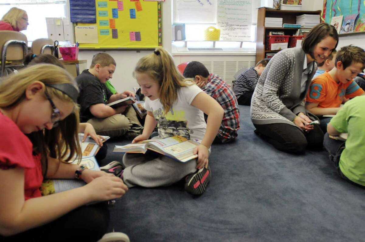 Watervliet Elementary School fourth grade teacher Kelly Webster, right, works with a group of students during a reading exercise Wednesday, Dec. 11, 2013, in Watervliet, N.Y. The students worked in small groups taking turns reading an article aloud. They would discuss what they read with group members. (Paul Buckowski / Times Union)