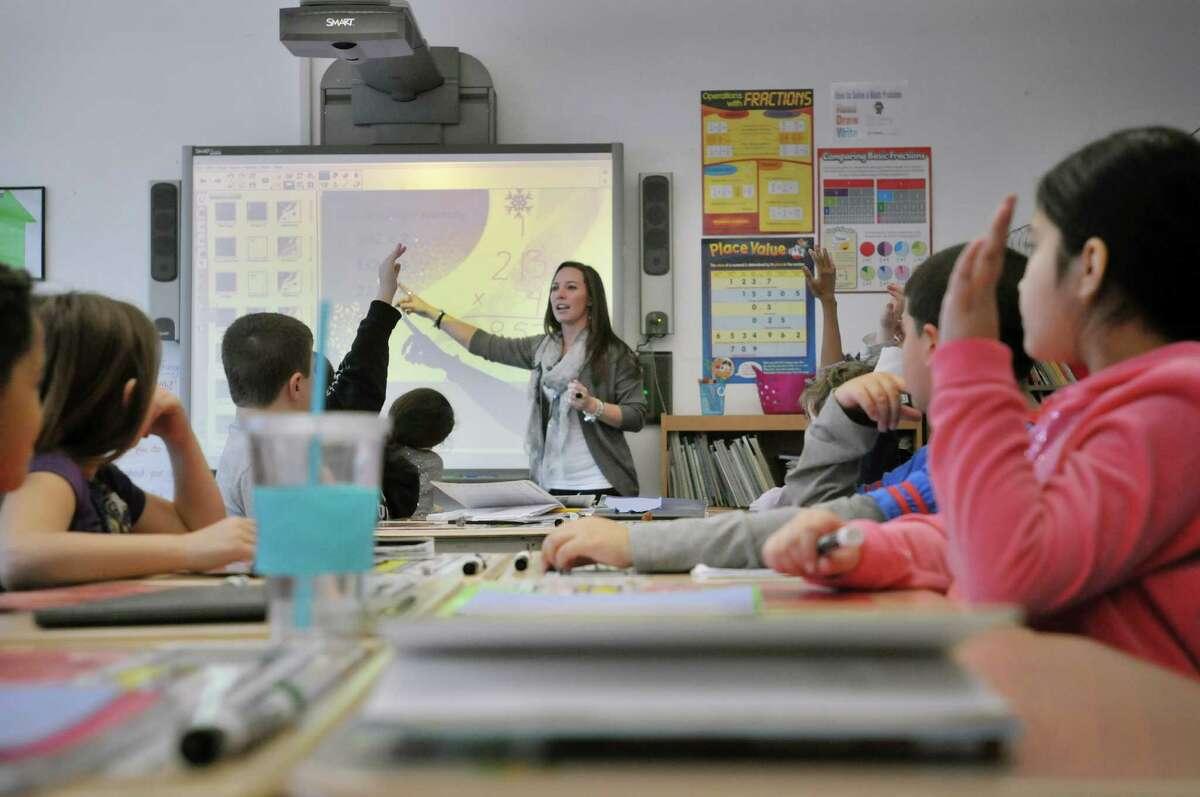 Watervliet Elementary School fourth grade teacher Khalan Heid looks for input from students as they work through a math problem Wednesday, Dec. 11, 2013, in Watervliet, N.Y. (Paul Buckowski / Times Union)