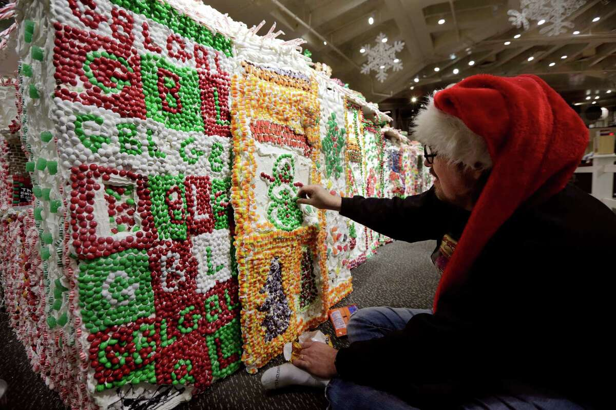 Chef and GingerBread Lane creator Jon Lovitch applies candies to the base of his annual showpiece, in the New York Hall of Science, in the Queens borough of New York, Thursday, Dec. 12, 2013. The 1.5-ton, 300-square-foot village that is made entirely of edible gingerbread, royal icing, and candy, has been acknowledged as the largest gingerbread village in the world by the 2014 Guinness World Records. (AP Photo/Richard Drew) ORG XMIT: NYRD114
