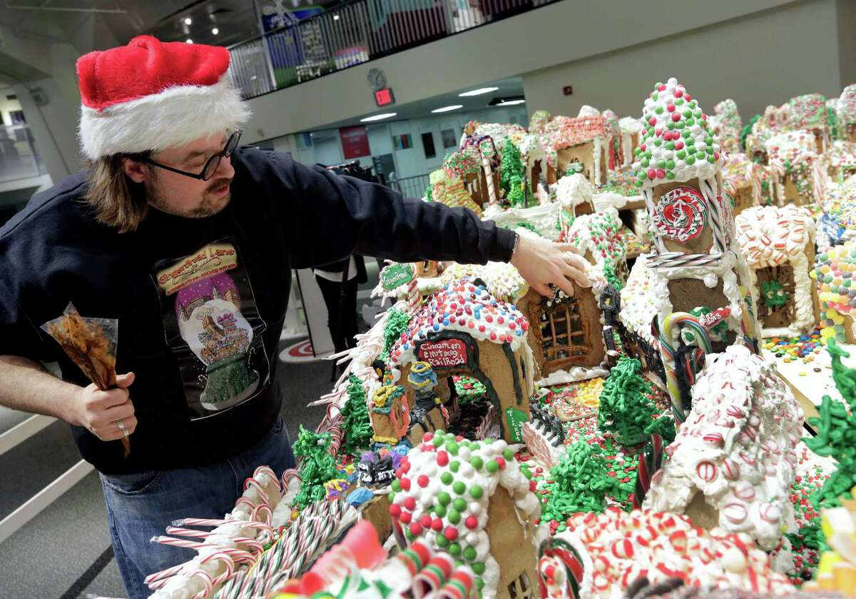 Chef and GingerBread Lane creator Jon Lovitch repairs one of the gingerbread houses of his annual showpiece, in the New York Hall of Science, in the Queens borough of New York, Thursday, Dec. 12, 2013. The 1.5-ton, 300-square-foot village that is made entirely of edible gingerbread, royal icing, and candy, has been acknowledged as the largest gingerbread village in the world by the 2014 Guinness World Records. (AP Photo/Richard Drew) ORG XMIT: NYRD116