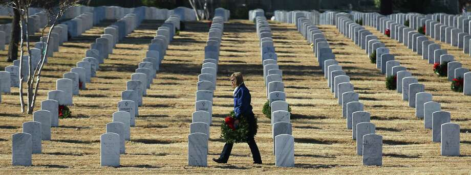 Krisanna Bradley of Greater Texas Livery - a motorcycle hearse service -  carries a wreath to be placed on a headstone at Fort Sam Houston National Cemetery on Saturday, Dec. 14, 2013. Families and volunteers were expected to place over 16,000 Christmas wreaths at the cemetery. Photo: Kin Man Hui, San Antonio Express-News / ©2013 San Antonio Express-News