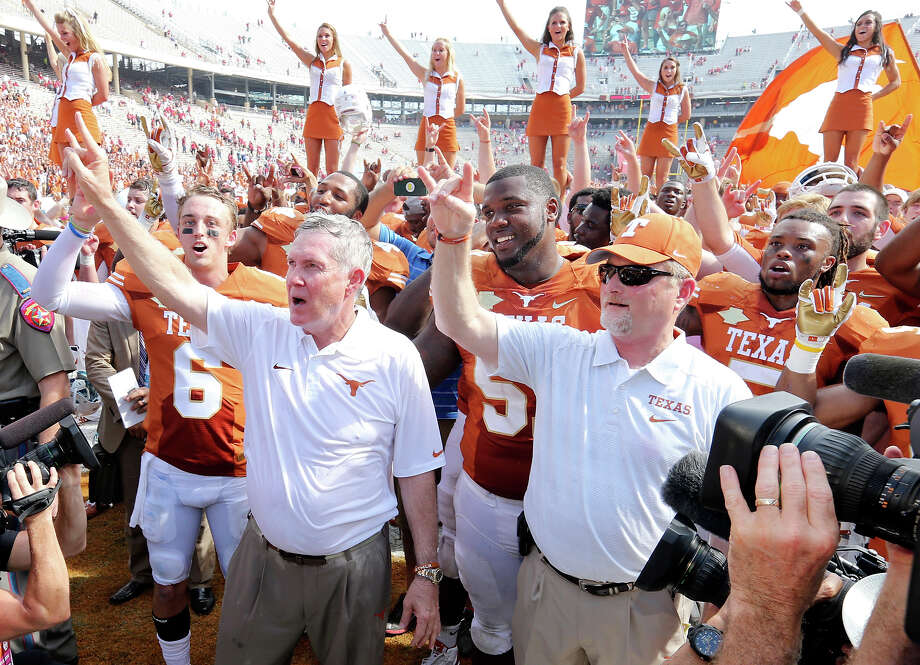 Texas Longhorns' Case McCoy (left), head coach Mack Brown (center) and others celebrate after the Red River Rivalry against the Oklahoma Sooners Saturday Oct. 12, 2013 at Cotton Bowl Stadium in Dallas, Tx. The Longhorns won 36-20. Photo: Edward A. Ornelas, San Antonio Express-News / © 2013 San Antonio Express-News