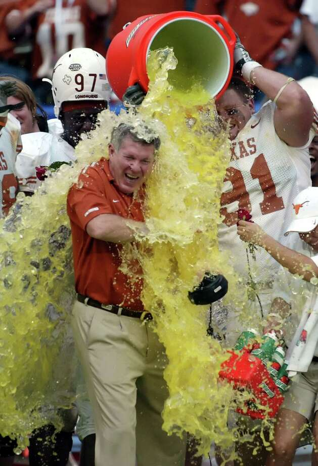 Texas Longhorns head Coach Mack Brown is doused with sports drink by his players after the Longhorns defeated the Colorado Buffaloes 70-3 to win the Big 12 Championship in Houston, Texas December 3, 2005. REUTERS/Richard Carson Photo: RICHARD CARSON, REUTERS / X01366