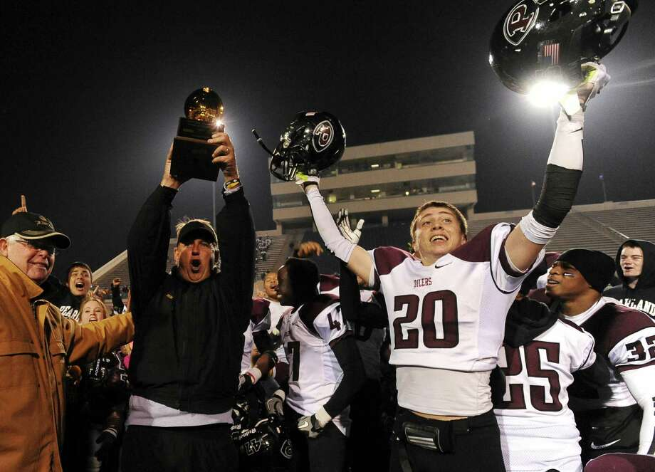 Head coach Tony Heath of Pearland hold up the Class 5A Division I state semifinal victory trophy after his team defeated Madison, 38-34, at Waco ISD Stadium on Saturday, Dec. 14, 2013. Conner Chidester is at right. Photo: Billy Calzada, San Antonio Express-News / San Antonio Express-News