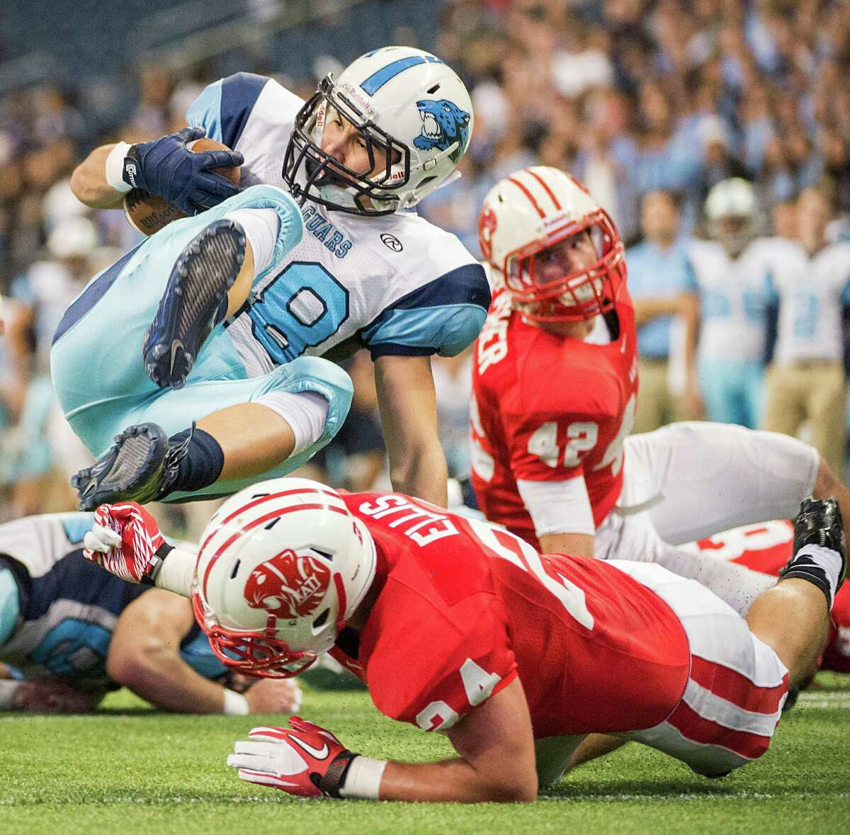 Johnson wide receiver Santana Barrera (28) is knocked off his feet for a loss by Katy linebacker Jason Ellis (24) during the first half of a Class 5A state semifinal high school football playoff game at Reliant Stadium on Saturday, Dec. 14, 2013, in Houston.