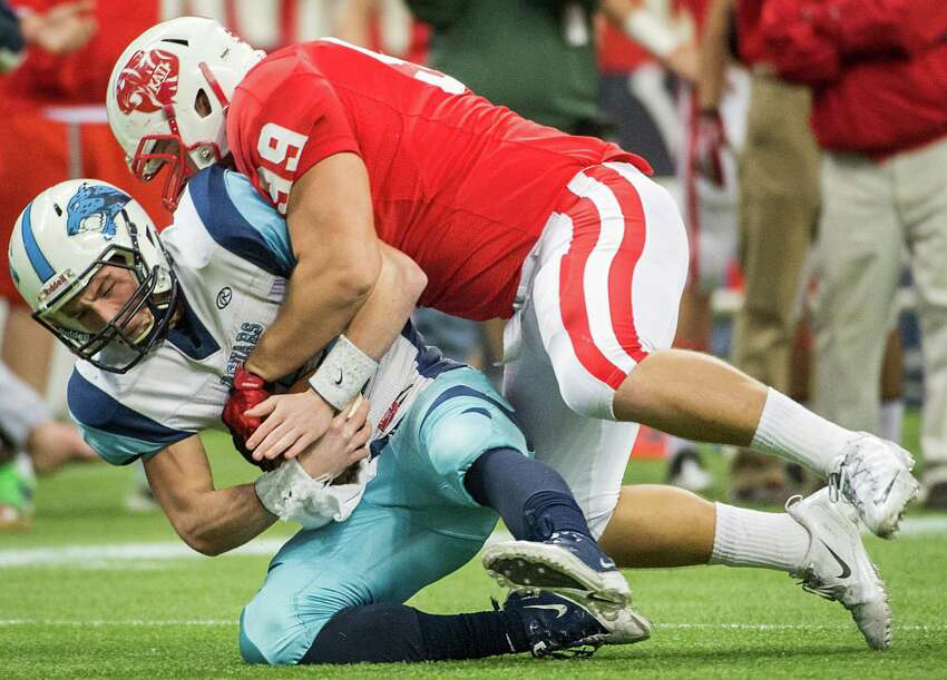 Johnson quarterback Hunter Rittimann (12) is sacked by Katy defensive lineman Jesse Brown (99) during the first half of a Class 5A state semifinal high school football playoff game at Reliant Stadium on Saturday, Dec. 14, 2013, in Houston.