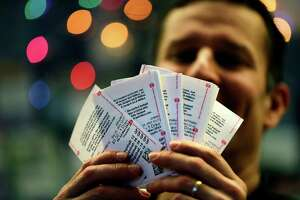 Chad Cuneo displays Mega Millions tickets he purchased at a newsstand Friday in Philadelphia. Tickets will be in high demand for Tuesday's drawing.