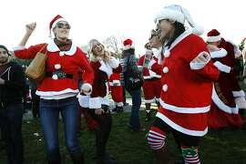 (L-R) Erin Nixon, Michelle Devaux and Ann Duong dance to a Mariah Carey Christmas song at Duboce Park during Santa Con 2013 in San Francisco, CA, Saturday, December 14, 2013.