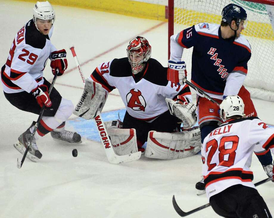 Devils'  goalie #31 Scott Wedgewood, center, stops a against Hartford shot during Saturday's game at the Times Union Center  Dec. 14, 2013, in Albany, NY.  (John Carl D'Annibale / Times Union) Photo: John Carl D'Annibale / 00025033A