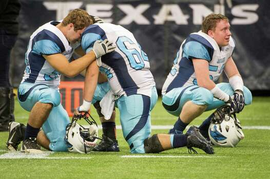 Johnson linebacker Chris Prevost, left, offensive lineman Alvert Meza, center, and defensive lineman Reid Graber kneel on the field after a loss to Katy in a Class 5A state semifinal high school football playoff game at Reliant Stadium on Saturday, Dec. 14, 2013, in Houston. Katy won the game 52-0. Photo: Smiley N. Pool, Houston Chronicle / © 2013  Houston Chronicle