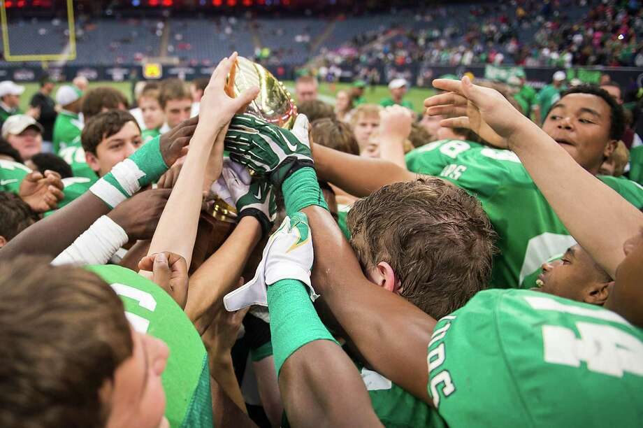 Brenham players reach for a state semifinal championship trophy after their victory over Calhoun in class 4A high school football playoff game at Reliant Stadium on Saturday, Dec. 14, 2013, in Houston. Photo: Smiley N. Pool, Houston Chronicle / © 2013  Houston Chronicle