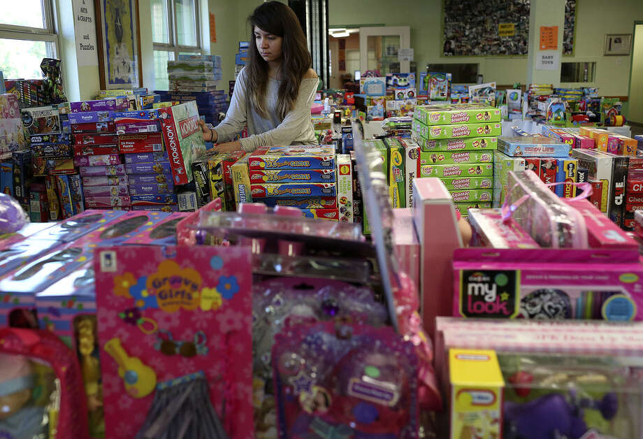Edison High student Angelica Benites, 17, helps set up the Inner City Development's Christmas toy sale, in which donated toys will be sold Sunday at 90 percent off the original price. Photo: Lisa Krantz / San Antonio Express-News / San Antonio Express-News