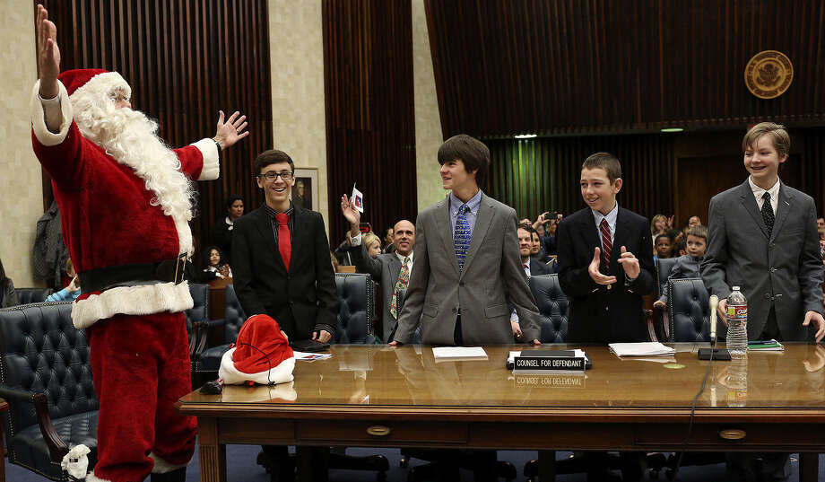 Santa Claus, also known as Bob Raymond, celebrates his not guilty verdict with his defense team of (from left), Jack Kenner, 14; Wesley Kirlin, 14; Harry Ware, 14; and Bailey Cole, 14. Photo: Lisa Krantz / San Antonio Express-News / San Antonio Express-News