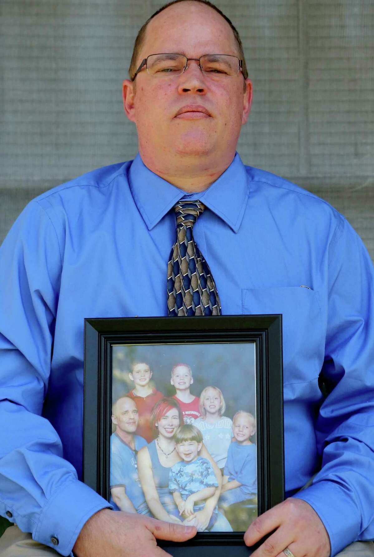 David Brasse, holding a family portrait on his porch in Alvin, was at work the day Sarah died and didn't see his daughter until her body was at the hospital.
