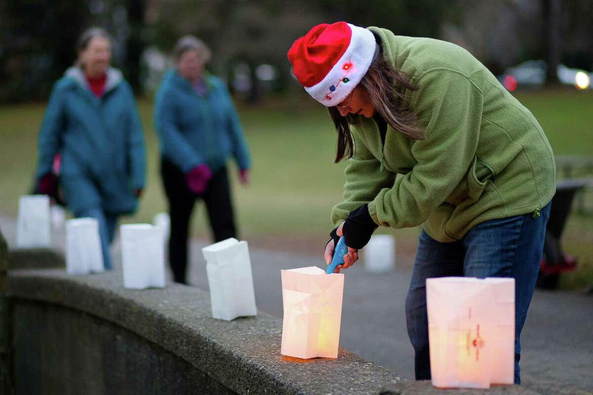 Lisa Stuebing, right, of the Green Lake Chamber of Commerce, lights candles in preparation for the annual Green Lake Pathway of Lights Saturday, Dec. 14, 2013, in Seattle.