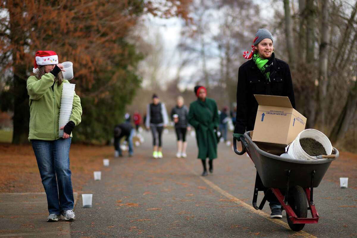 Conner Cayson, right, and Lisa Stuebing, left, of the Green Lake Chamber of Commerce, set up candles in preparation for the annual Green Lake Pathway of Lights Saturday, Dec. 14, 2013, in Seattle.