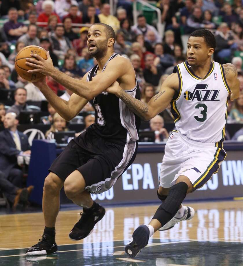 San Antonio Spurs' Tony Parker, left, drives the basket as Utah Jazz's Trey Burke (3) defends in the first half of an NBA basketball game on Saturday, Dec. 14, 2013, in Salt Lake City. (AP Photo/Kim Raff) Photo: Associated Press