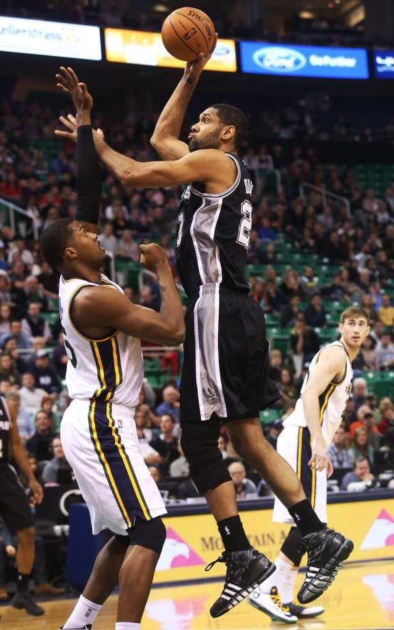 San Antonio Spurs' Tim Duncan, right, shoots the ball as Utah Jazz's Derrick Favors, left, defends in the first half of an NBA basketball game on Saturday, Dec. 14, 2013, in Salt Lake City. (AP Photo/Kim Raff) Photo: Kim Raff, Associated Press