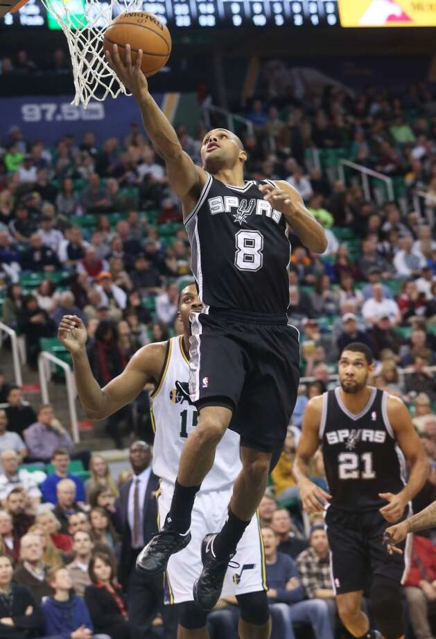 San Antonio Spurs' Patty Mills (8) attempts a layup as Utah Jazz's Derrick Favors, back, looks on in the first half of an NBA basketball game on Saturday, Dec. 14, 2013, in Salt Lake City. (AP Photo/Kim Raff) Photo: Kim Raff, Associated Press