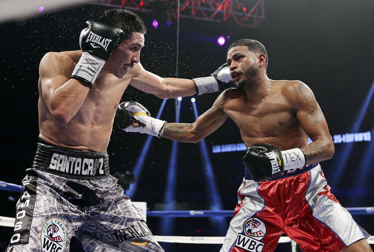 """Leo Santa Cruz (left) and Cesar Seda trade punches during their WBC super bantamweight fight. """"I want an immediate rematch,"""" Seda said after he lost."""