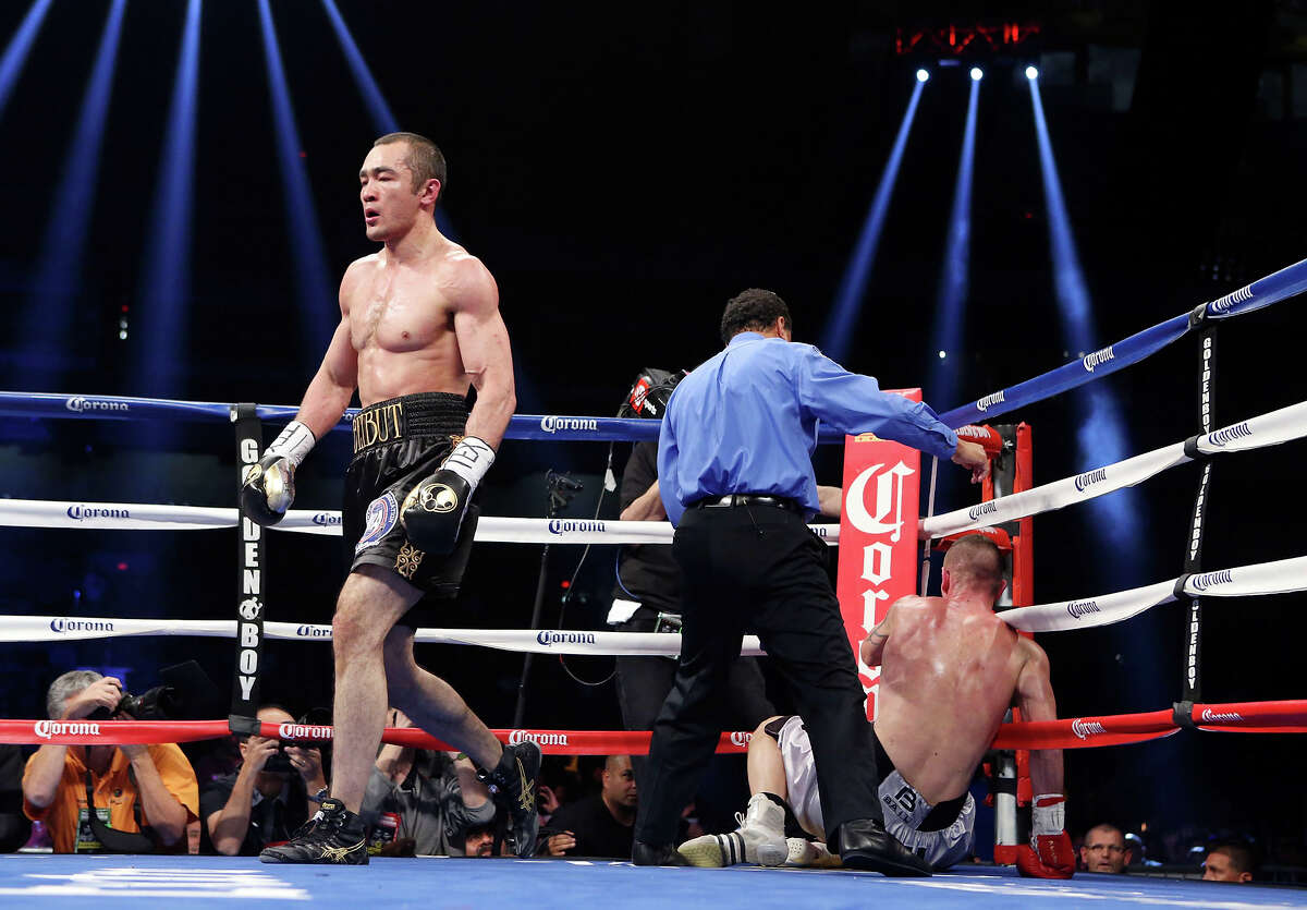 """Beibut Shumenov (left) walks away from Tamas Kovacs (on ground) during their WBA Super World/IBA Light Heavyweight fight part of the """"Danger Zone"""" boxing card Saturday Dec. 14, 2013 at the Alamodome. Shumenov won by TKO."""