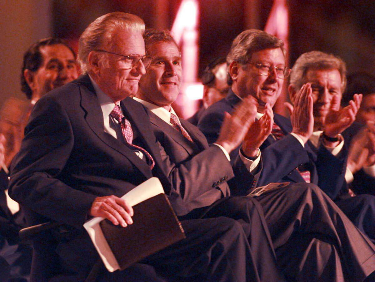 Billy Graham receives applause as he leaves his chair with his Bible to go speak on the first day of the crusade at the Alamodome, Thursday, April 3, 1997. On his right are Texas Gov. George W. Bush and San Antonio Mayor Bill Thornton.