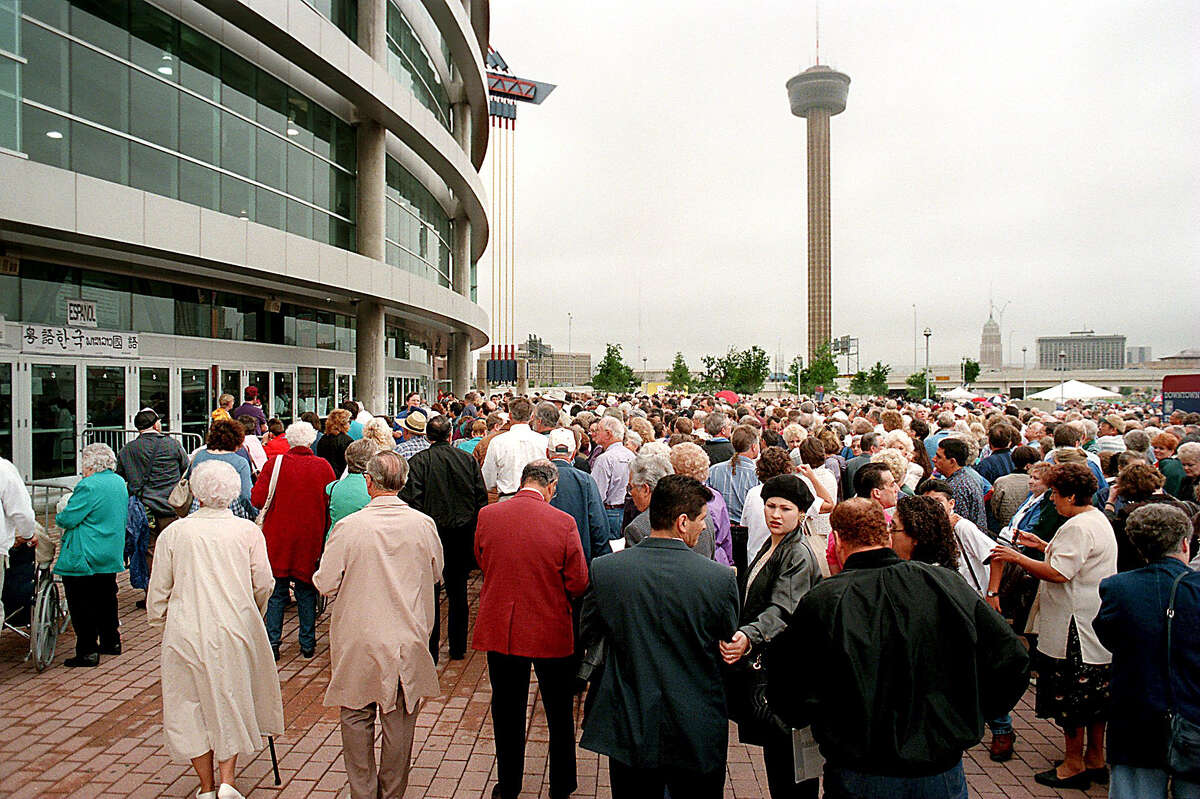 Thursday's gray skies and rain didn't seem to bother the crowds as they wait outside the north entrance of the Alamodome on April 3, 1997, for the Billy Graham Crusade to begin.