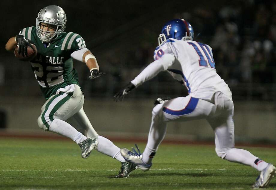 De La Salle's John Velasco, who rushed for 144 yards and four touchdowns, runs past Folsom's Cole Thompson. Photo: Leah Millis, The Chronicle