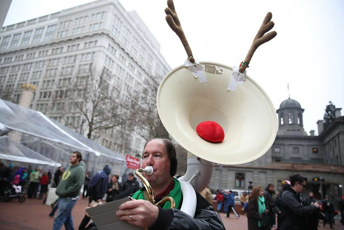 Bill Lafleur warms up before the 23rd Annual Tuba Christmas Concert. The heavy-metal sound of nearly 300 tuba and euphonium players filled Pioneer Courthouse Square in Portland, Ore., with holiday cheer on Saturday, Dec. 14, 2013. (AP Photo/The Oregonian, Faith Cathcart)