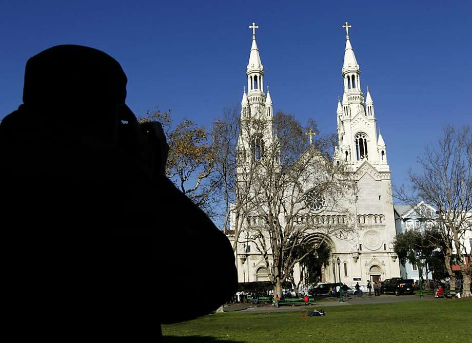 A tourist visiting from China snaps a photo of Saints Peter and Paul Church from Washington Square park in the North Beach neighborhood of San Francisco, Calif. on Thursday, Dec. 12, 2013. Photo: Paul Chinn, The Chronicle