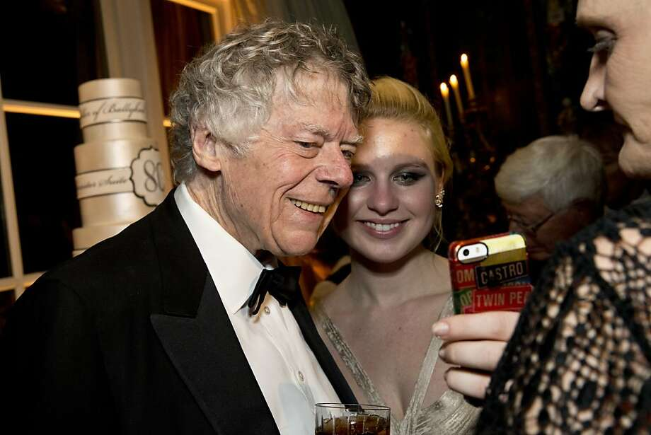 Ivy Getty shows her grandfather Gordon Getty a photo during his 80th birthday party at the Getty's home in Pacific Heights in San Francisco, Calif., on Saturday, December 14, 2013.  Getty happens to have the same birthday as her grandfather. Photo: Laura Morton, Special To The Chronicle