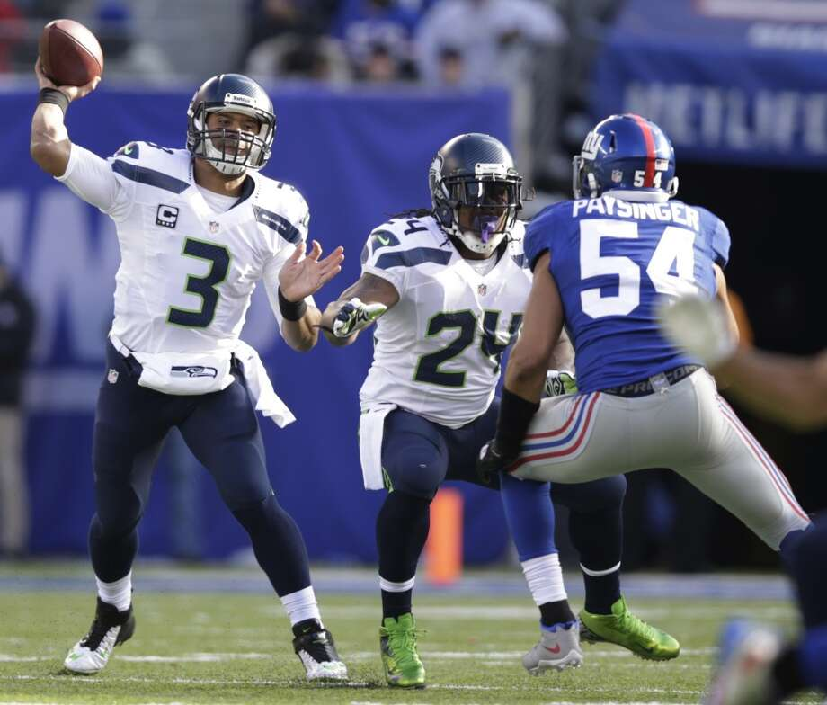 Seattle Seahawks quarterback Russell Wilson (3) throws a pass as running back Marshawn Lynch (24) blocks New York Giants outside linebacker Spencer Paysinger (54) during the first half of an NFL football game on Sunday, Dec. 15, 2013, in East Rutherford, N.J. (AP Photo/Kathy Willens) Photo: Kathy Willens, AP