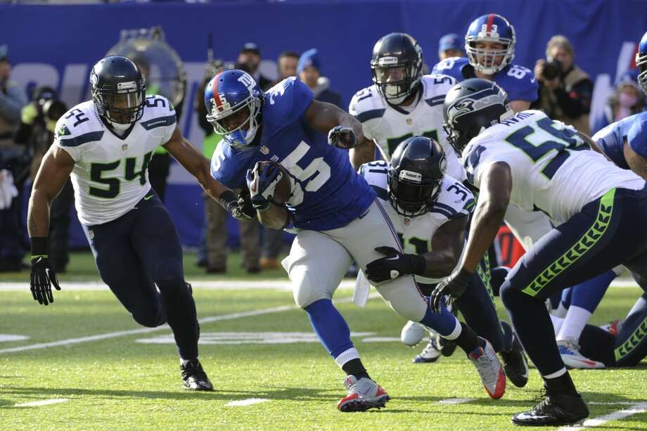 New York Giants running back Andre Brown (35) runs with the ball as Seattle Seahawks strong safety Kam Chancellor (31) makes the hit on him during the first half of an NFL football game, Sunday, Dec. 15, 2013, in East Rutherford, N.J. (AP Photo/Bill Kostroun) Photo: Bill Kostroun, AP