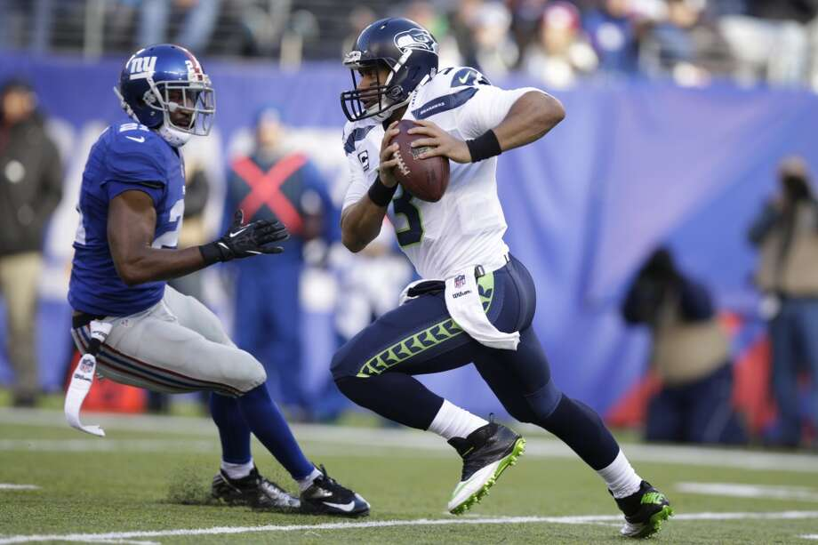 Seattle Seahawks quarterback Russell Wilson (3) runs with the ball against New York Giants free safety Ryan Mundy (21) during the first half of an NFL football game, Sunday, Dec. 15, 2013, in East Rutherford, N.J. (AP Photo/Kathy Willens) Photo: Kathy Willens, AP