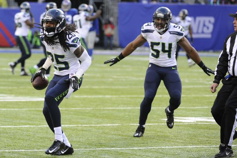 Seattle Seahawks cornerback Richard Sherman (25) and middle linebacker Bobby Wagner (54) celebrate after Sherman intercepted a pass from New York Giants quarterback Eli Manning during the first half of an NFL football game, Sunday, Dec. 15, 2013, in East Rutherford, N.J. (AP Photo/Bill Kostroun) Photo: Bill Kostroun, AP