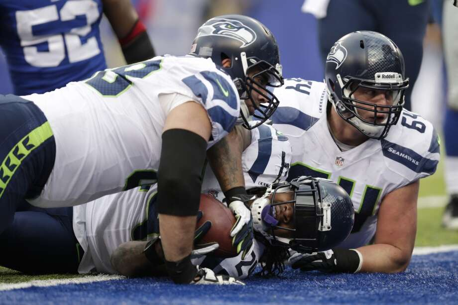 Seattle Seahawks running back Marshawn Lynch, center, lays over the goal line with teammates Breno Giacomini, left, and J.R. Sweezy after Lynch scored on a touchdown run against the New York Giants during the first half of an NFL football game, Sunday, Dec. 15, 2013, in East Rutherford, N.J. (AP Photo/Kathy Willens) Photo: Kathy Willens, AP
