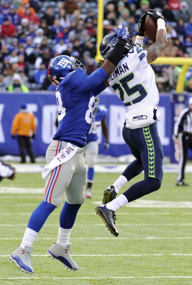 Seattle Seahawks cornerback Richard Sherman, right, intercepts a pass from New York Giants quarterback Eli Manning intended for wide receiver Hakeem Nicks, left, during the first half of an NFL football game on Sunday, Dec. 15, 2013, in East Rutherford, N.J. (AP Photo/Bill Kostroun) Photo: Bill Kostroun, AP