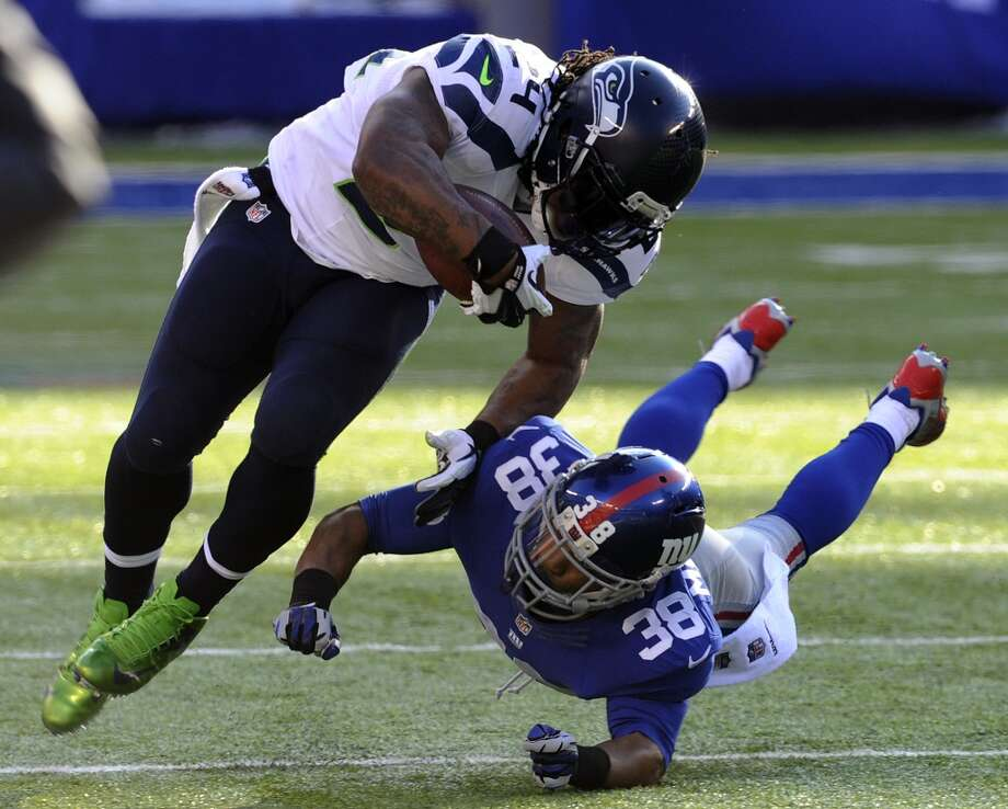 Seattle Seahawks running back Marshawn Lynch (24) is hit by New York Giants cornerback Trumaine McBride (38) during the first half of an NFL football game on Sunday, Dec. 15, 2013, in East Rutherford, N.J. (AP Photo/Bill Kostroun) Photo: Bill Kostroun, AP