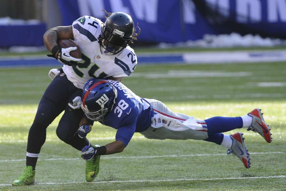 Seattle Seahawks running back Marshawn Lynch (24) is hit by New York Giants cornerback Trumaine McBride (38) during the first half of an NFL football game, Sunday, Dec. 15, 2013, in East Rutherford, N.J. (AP Photo/Bill Kostroun) Photo: Bill Kostroun, AP