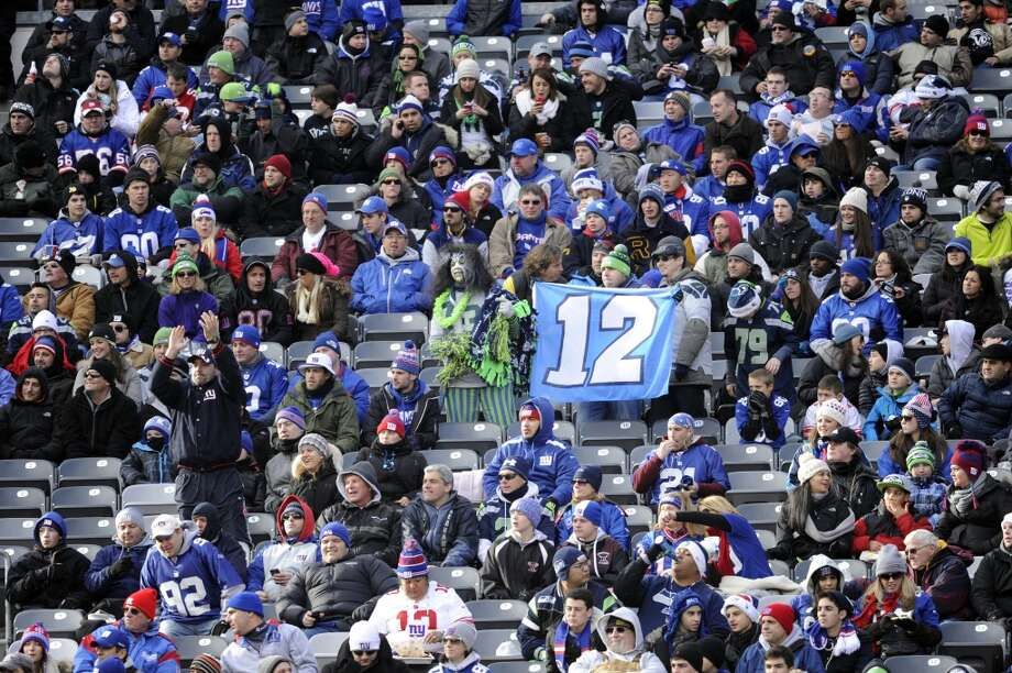 A Seattle Seahawks fan holds a flag for the 12th Man during the first half of an NFL football game between the Seahawks and the New York Giants, Sunday, Dec. 15, 2013, in East Rutherford, N.J. (AP Photo/Bill Kostroun) Photo: Bill Kostroun, AP