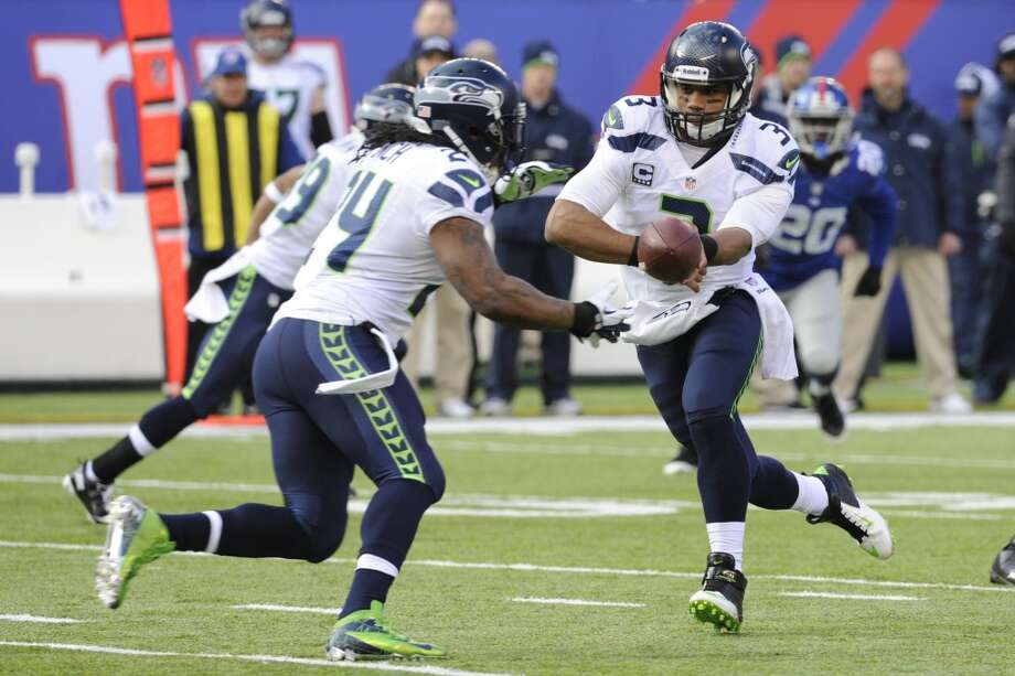 Seattle Seahawks quarterback Russell Wilson (3) hands off to running back Marshawn Lynch (24) during the first half of an NFL football game against the New York Giants, Sunday, Dec. 15, 2013, in East Rutherford, N.J. (AP Photo/Bill Kostroun) Photo: Bill Kostroun, AP