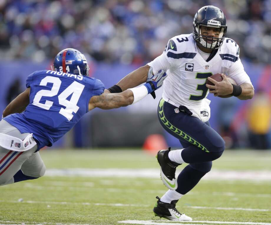 Seattle Seahawks quarterback Russell Wilson (3) fends off New York Giants cornerback Terrell Thomas (24) during the first half of an NFL football game, Sunday, Dec. 15, 2013, in East Rutherford, N.J. (AP Photo/Kathy Willens) Photo: Kathy Willens, AP
