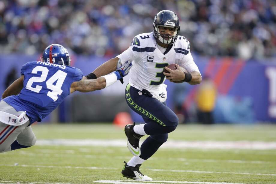Seattle Seahawks quarterback Russell Wilson (3) stiff arms New York Giants cornerback Terrell Thomas (24) during the first half of an NFL football game, Sunday, Dec. 15, 2013, in East Rutherford, N.J. (AP Photo/Kathy Willens) Photo: Kathy Willens, AP