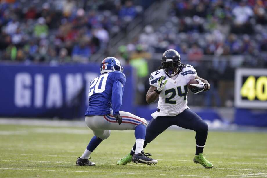 Seattle Seahawks running back Marshawn Lynch (24) runs with the ball as New York Giants cornerback Prince Amukamara (20) moves in for the tackle during the first half of an NFL football game, Sunday, Dec. 15, 2013, in East Rutherford, N.J. (AP Photo/Kathy Willens) Photo: Kathy Willens, AP