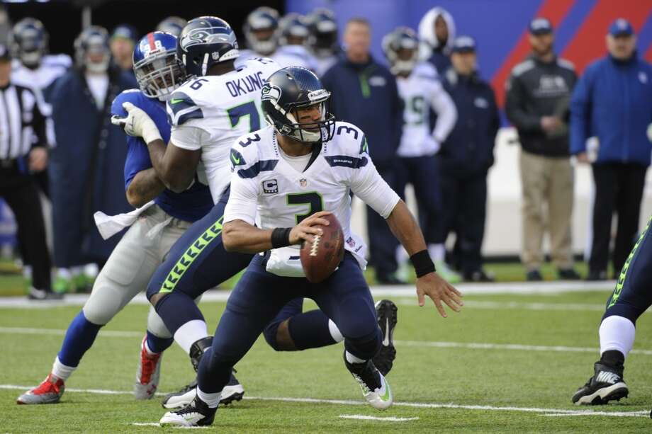 Seattle Seahawks quarterback Russell Wilson scrambles while looking to pass against the New York Giants during the first half of an NFL football game, Sunday, Dec. 15, 2013, in East Rutherford, N.J. (AP Photo/Bill Kostroun) Photo: Bill Kostroun, AP