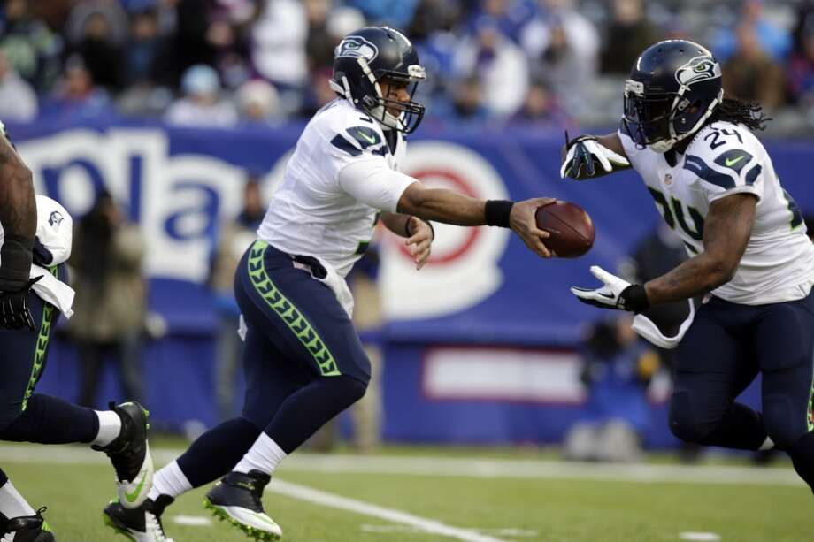 Seattle Seahawks quarterback Russell Wilson, left, hands off to running back Marshawn Lynch during the first half of an NFL football game against the New York Giants, Sunday, Dec. 15, 2013, in East Rutherford, N.J. (AP Photo/Kathy Willens) Photo: Kathy Willens, AP