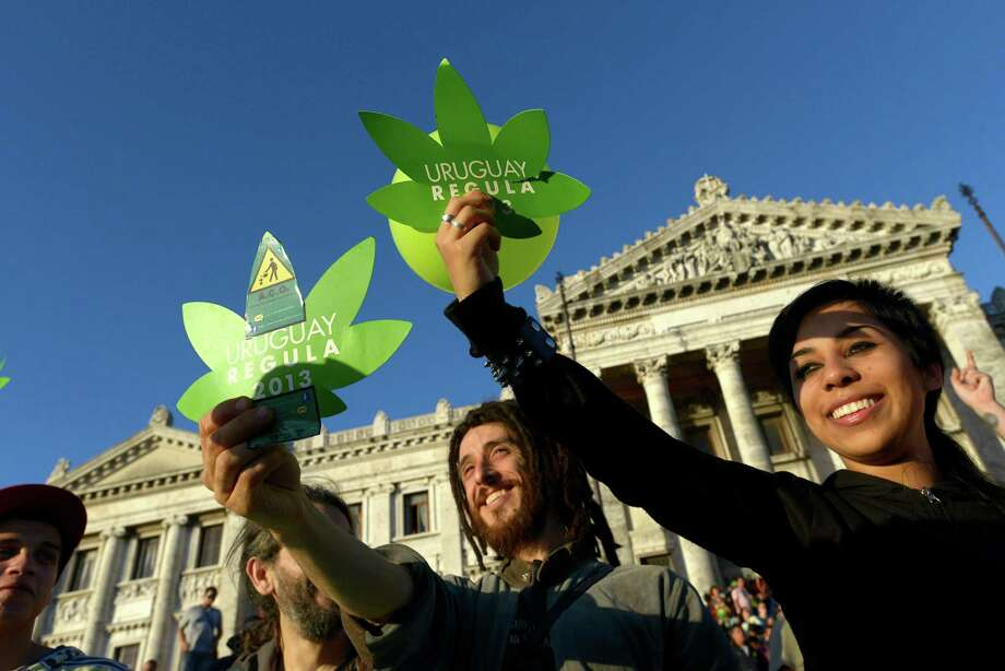 Activists gather in support of the legalization of marijuana outside the Congress building, as senators vote on a law to legalize the drug, in Montevideo, Uruguay, Tuesday, Dec. 10, 2013. Uruguay's Senate gave final congressional approval Tuesday to create the world's first national marketplace for legal marijuana, an audacious experiment that will have the government oversee production, sales and consumption of a drug illegal almost everywhere else. Photo: Matilde Campodonico, AP / AP2013