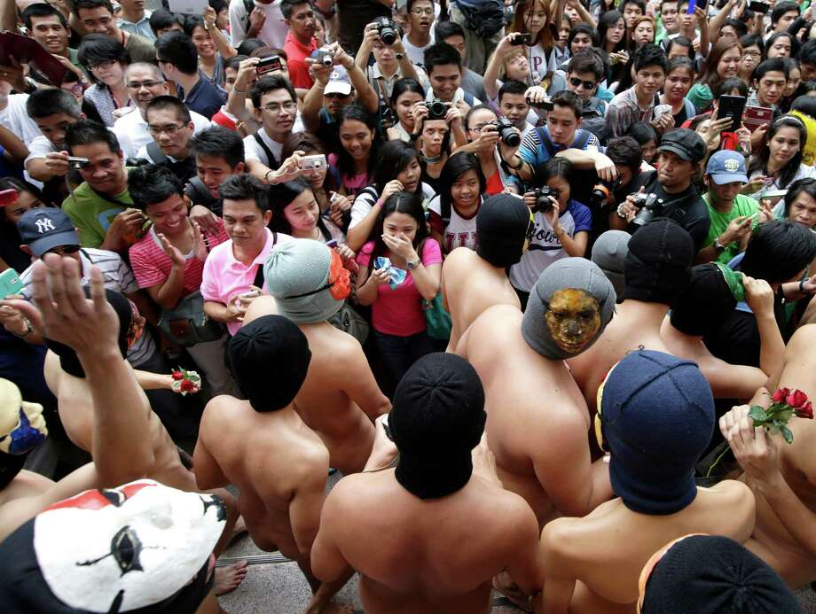 "Hundreds of students watch naked fraternity members from the country's premier state University of the Philippines, Diliman, in their annual festivities Friday, Dec. 13, 2013 at their campus at suburban Quezon city, northeast of Manila, Philippines. The annual ""Oblation Run"" evolved into a protest to draw the attention of the government with this year's theme of calling on the government to unite to fight corruption and to deal swiftly in times of calamities and natural disasters. Photo: Bullit Marquez, AP / AP"