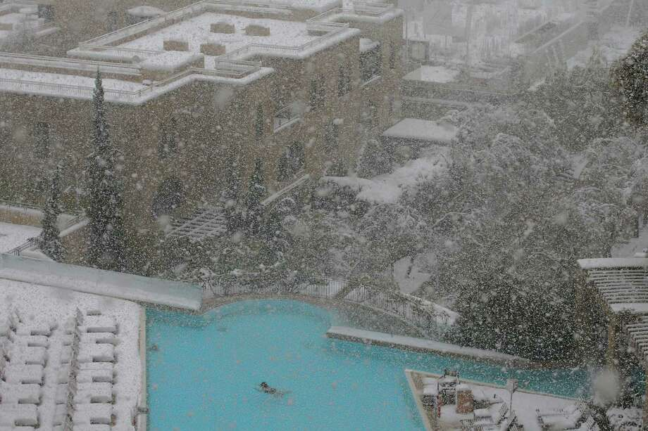 A woman swims in the pool at the David Citadel Hotel during a snowstorm in Jerusalem Friday, Dec. 13, 2013. A snowstorm of rare intensity blanketed the Jerusalem area and parts of the occupied West Bank on Friday, choking off the city and stranding hundreds in vehicles on impassable roads. Photo: Brian Snyder, AP / AP2013