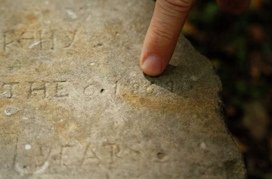 In this photo taken on Nov. 15, 2013, homeowner Craig Taylor points to the year engraved on a gravestone he found his backyard in Irving, Texas.  (AP Photo/The Dallas Morning News, Kye R. Lee)  Photo: Kye R. Lee, AP / The Dallas Morning News